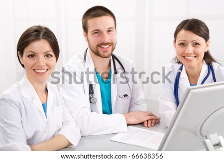 Smiling medical doctors on a workplace - stock photo