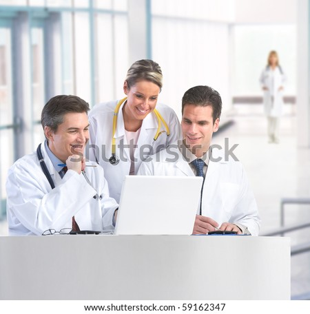 Smiling medical doctors with stethoscopes working with computer. - stock photo