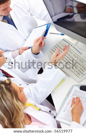 Smiling medical doctors working with a computer. - stock photo
