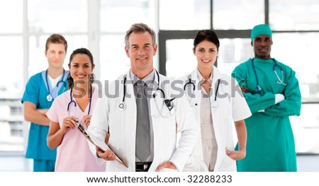 Smiling Medical team looking at the camera in hospital - stock photo