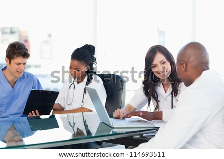 Smiling medical team working both on a laptop and a clipboard - stock photo