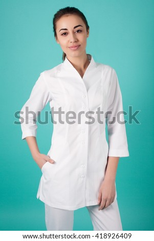 Smiling medical woman doctor.  Isolated over turquoise background - stock photo