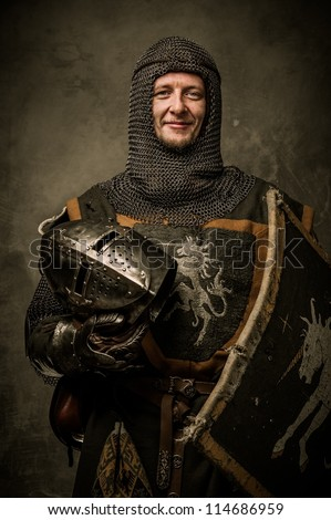 Smiling medieval knight  holding helmet - stock photo