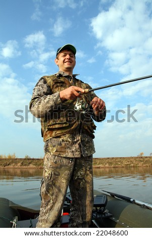 smiling men fishing with spinning on the river - stock photo