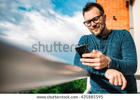 Smiling men typing text message - stock photo