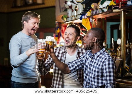 Smiling men with beer in pub - stock photo