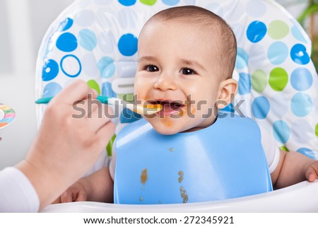 Smiling  messy baby likes to eat - stock photo