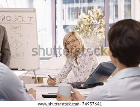 Smiling mid adult businesswoman sitting on team meeting, looking at camera.? - stock photo