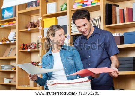 Smiling mid adult couple selecting papers in store - stock photo