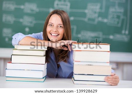 Smiling mid adult female teacher with two stack of books at classroom desk