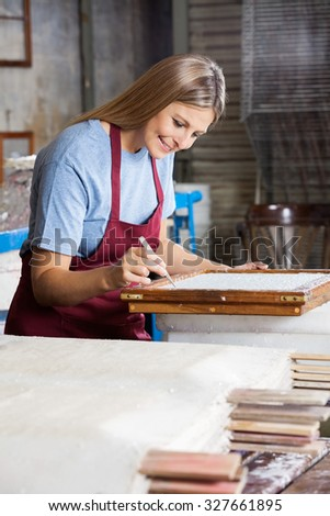 Smiling mid adult female worker cleaning paper using tweezers in factory - stock photo