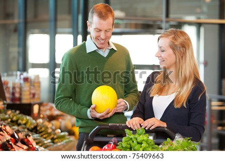 Smiling mid adult man holding fruit while standing with woman in shopping store - stock photo