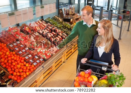 Smiling mid adult man pointing at vegetables while shopping with wife in grocery store - stock photo