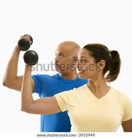 Smiling mid adult multi-ethnic man and woman exercising with dumbbells doing bicep curls. - stock photo