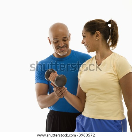 Smiling mid adult multiethnic man assisting mid adult multiethnic woman with dumbbells. - stock photo