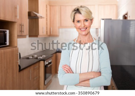 smiling mid age woman in kitchen with apron - stock photo