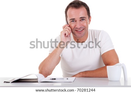 smiling middle-age man sitting at desk on the phone, on a white background. Studio shot - stock photo