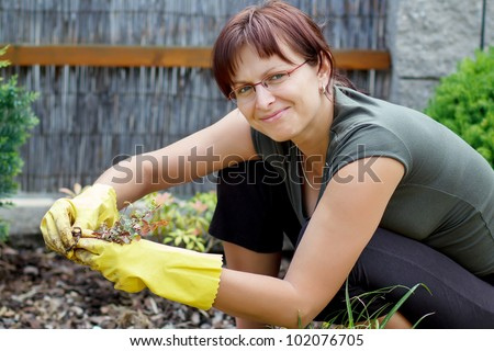 smiling middle age woman gardener with flowers outdoor in her garden - stock photo