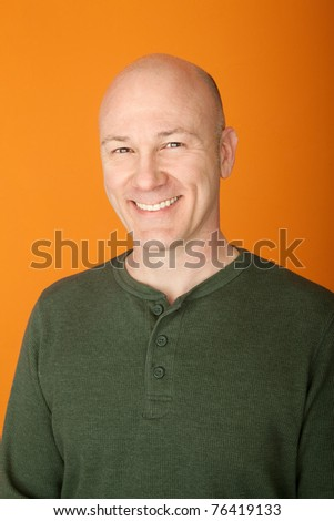 Smiling middle-aged bald Caucasian man on orange background - stock photo