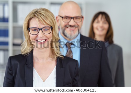Smiling middle aged beautiful female business person wearing eyeglasses and blue suit jacket in front of cheerful co-workers in office - stock photo