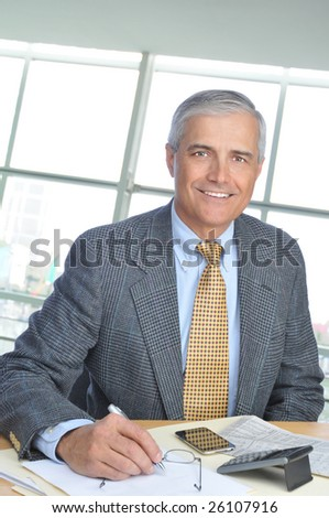 Smiling Middle Aged Businessman at desk in Modern Office Building