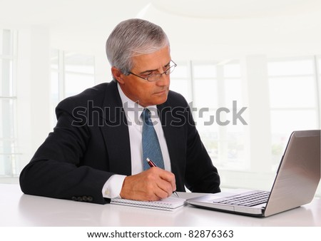 Smiling Middle Aged Businessman at desk using laptop computer with concerned expression. Horizontal format in modern office setting