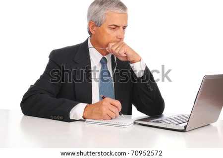 Smiling Middle Aged Businessman at desk using laptop computer with concerned expression isolated on white. - stock photo