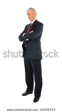 Smiling middle aged businessman in a suit and tie standing with his arms folded. Full length over a white background. - stock photo