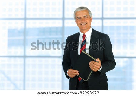 Smiling middle aged businessman in modern office setting holding a small binder. Horizontal Format. - stock photo
