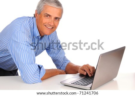 Smiling Middle Aged Businessman leaning on desk using laptop computer isolated on white. - stock photo