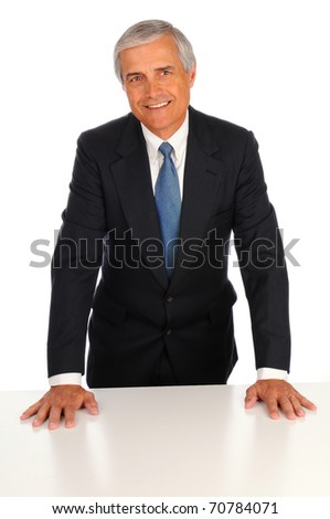 Smiling Middle Aged Businessman leaning on desk with both hands on a white background