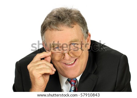 Smiling middle aged businessman looks over his glasses. - stock photo