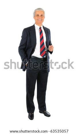Smiling middle aged businessman wearing a suit standing with one hand in his pocket and the other holding his eye glasses. Full length over a white background. - stock photo