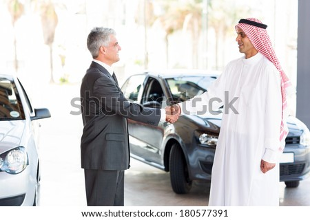 smiling middle aged car dealer handshake with arabian man - stock photo