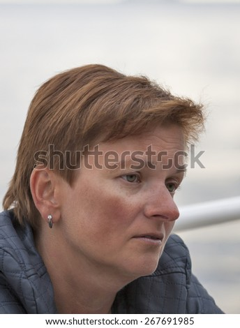 smiling middle aged caucasian tanned sad woman outdoor portrait - stock photo