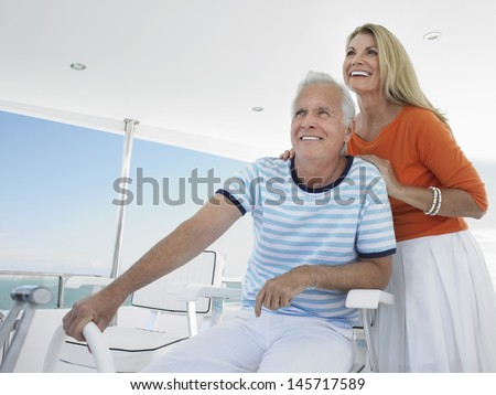 Smiling middle aged couple at helm of yacht - stock photo