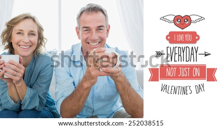 Smiling middle aged couple sitting on the couch having coffee against cute valentines message - stock photo