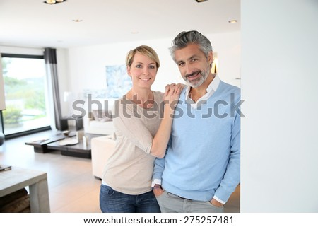 Smiling middle-aged couple standing in brand new home - stock photo
