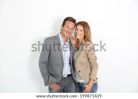 Smiling middle-aged couple standing on white background - stock photo