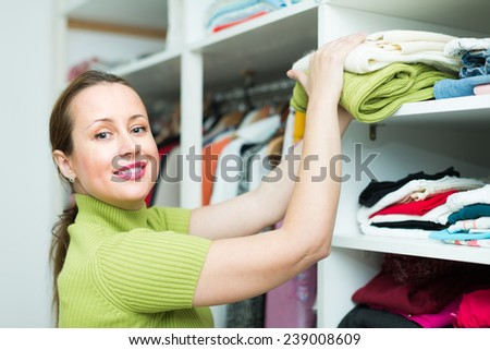 Smiling middle-aged female customer choosing apparel on shelves at store - stock photo