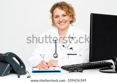 Smiling middle aged female doctor sitting in clinic writing on notepad