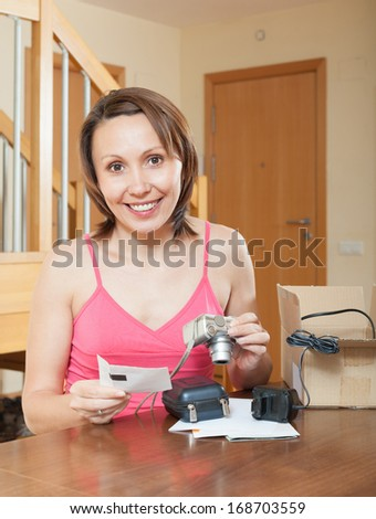 Smiling middle-aged girl unpacking new compact digital camera