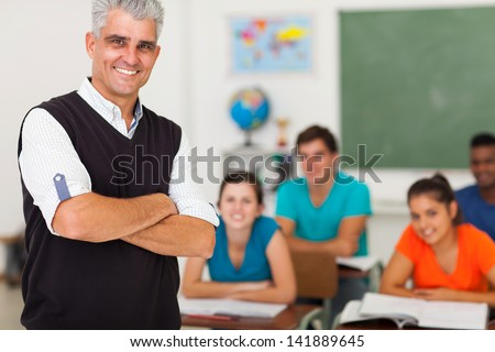 smiling middle aged high school teacher with arms folded standing in front of the class - stock photo