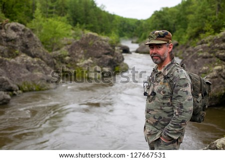Smiling middle aged hiker in a mountain river. Russia. Primorskiy kray. - stock photo