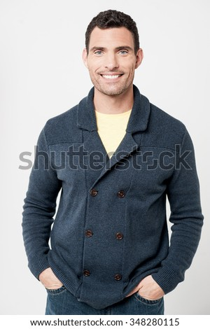 Smiling middle aged man posing with his hands in pockets