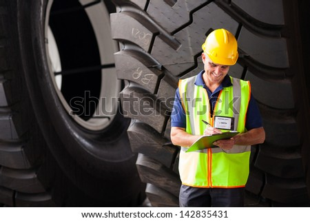 smiling middle aged shipping worker in warehouse - stock photo