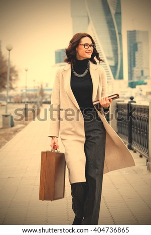 smiling middle-aged woman in a bright coat, with a wooden case and a book in his hands outdoors. close-up. instagram image filter retro style