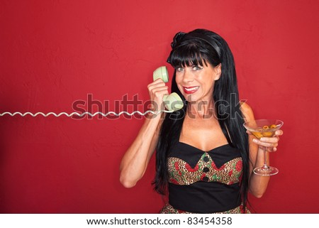 Smiling middle-aged woman on phone with a martini