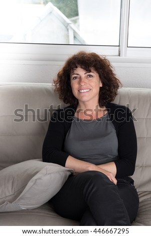 smiling middle aged woman sitting on couch - stock photo