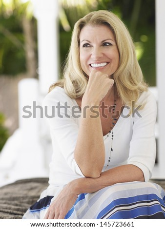 Smiling middle aged woman sitting on verandah and looking away - stock photo